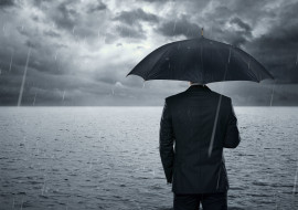 Businnessman standing in the dramatic ocean befre storm